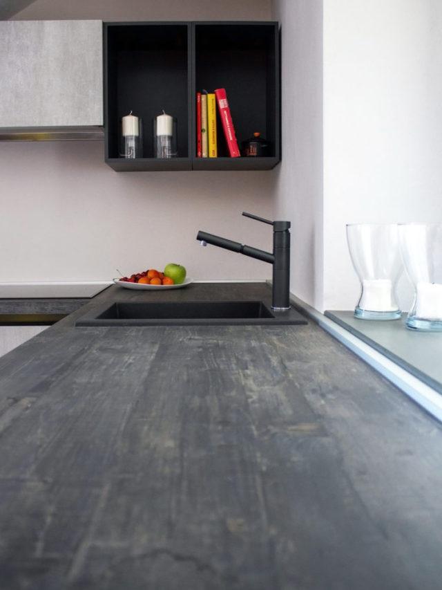 Fotografia di dettaglio di cucina con piano di lavoro scuro effetto cemento e lavandino monovasca.