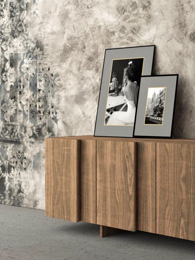 Render di credenza in legno caratterizzata da un gioco di luci ed ombre sul prospetto frontale dato dal diverso spessore delle ante a battente. E' inserita in un ambiente dallo stile industriale, con pavimento in cemento e parete usurata dal tempo.