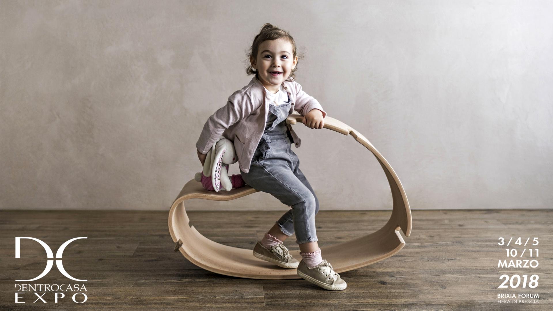 Locandina dell'esposizione del prodotto YaWood di Argo4 presso la fiera DentroCasa Expo a Brescia. Una bambina di un anno e mezzo sorride felice seduta sul cavallo a dondolo in legno curvato Yawood.