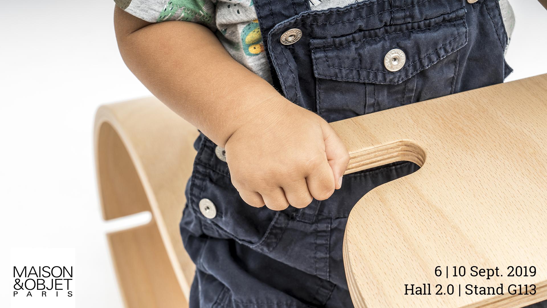 Locandina dell'esposizione del prodotto YaWood di Argo4 presso Maison&Objet a Parigi. Dettaglio della mano di un bambino che afferra del manubrio di YaWood.