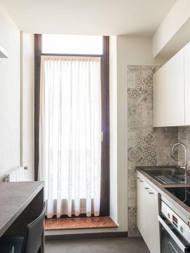 Fotografia di cucina molto luminosa grazie ai colori chiari dell'arredo e alla portafinestra. Il mobile cucina è sul lato destro e sulla parete frontale c'è un bancone snack con sgabelli.