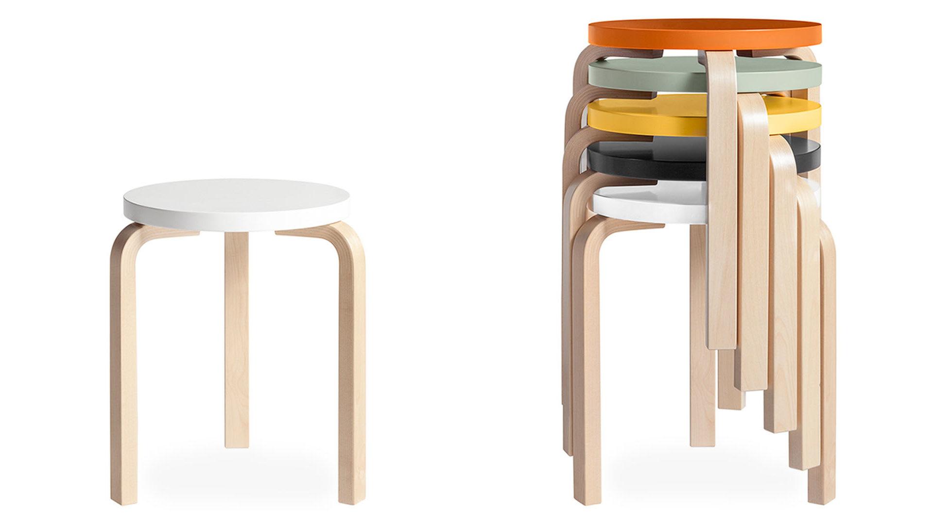 """Fotografia dello sgabello Stool60 caratterizzato da una seduta circolare, disponibile in diversi colori, e tre gambe in legno piegate a """"L""""."""
